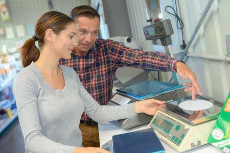 grams: Man and woman calibrating scales
