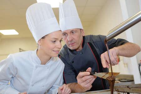 artisans: two artisans making chocolate sauce