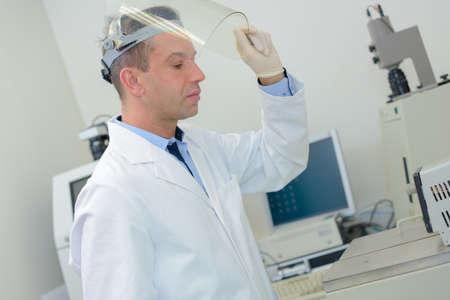 Lab technician raising visor of mask