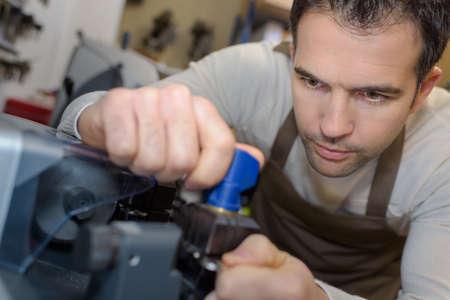 experienced operator: Cobbler setting up key cutting machine Stock Photo