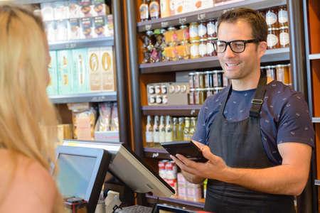 shop assistant: Shop assistant using calculator