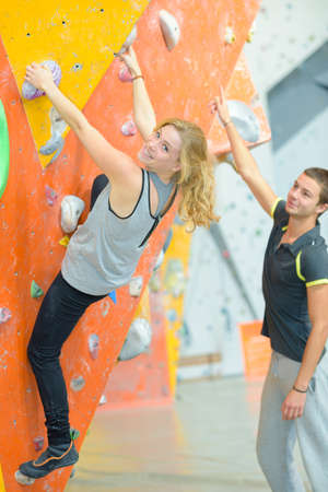 recreational climbing: instructor guiding woman on rock climbing wall at the gym Stock Photo