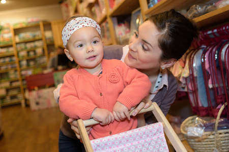 niño empujando: young mother her daughter shopping at the toy store Foto de archivo