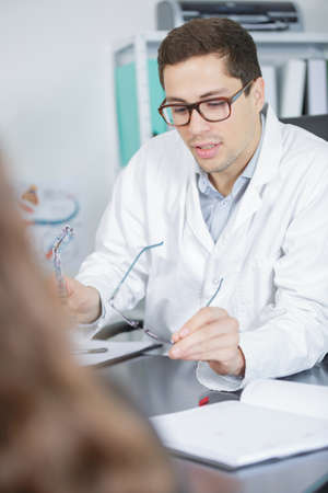 young skilled ophthalmologist talking to female patient Stock Photo