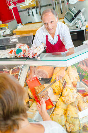 serf: Butcher serving a customer with pate