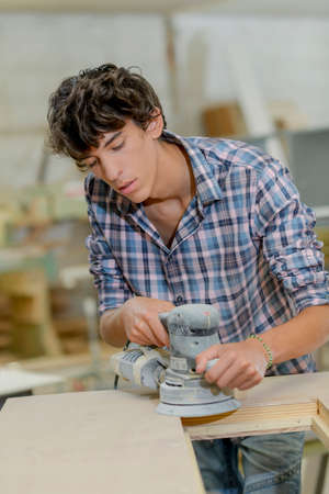Young carpenter using a sander