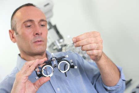 Optician putting lens into eyetest glasses Stock Photo
