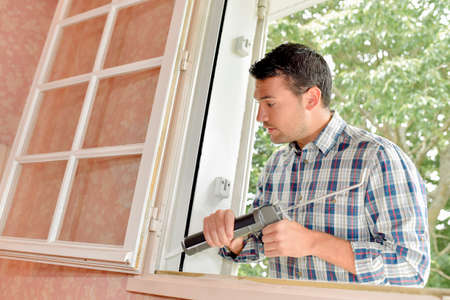 sealant: Man putting sealant around window frame
