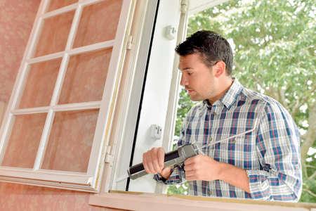 Man putting sealant around window frame