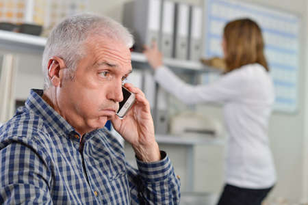 exasperated: Man on telephone, exasperated expression Stock Photo