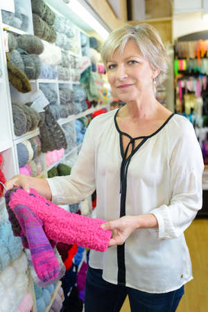 clothing shop: Woman in shop looking at knitted childs clothing