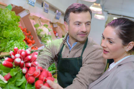 grocer: Grocer and customer looking a radishes