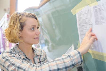 Vrouw lezing lijst geplaatst op muur