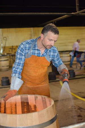 dampen: Cooper spraying water on barrell