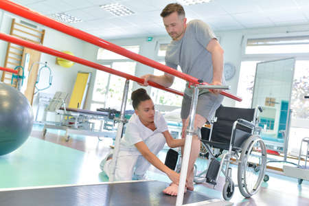 Occupational therapist helping patient to walk Banque d'images