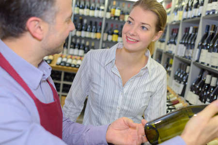 suggesting: Wine merchant suggesting bottle to customer