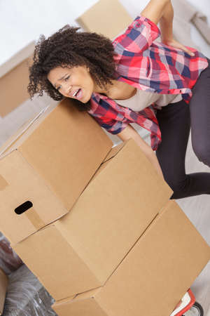 woman in pain: woman with backache while lifting box
