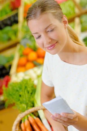 grocers: Lady in grocers looking at shopping list