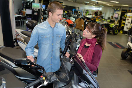 a two wheeled vehicle: Young couple in scooter showroom
