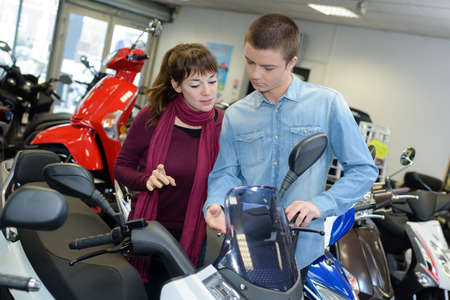 motor cycle: Young couple looking at modern scooter