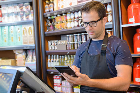 shop keeper: Shop keeper using calculator