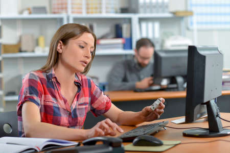 toiling: Woman sat at her desk Stock Photo