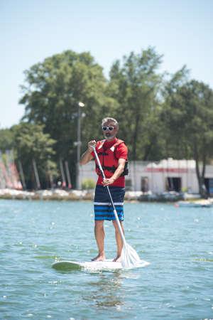 tabla de surf: el hombre disfruta de un paseo en el lago con paddleboard