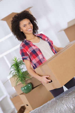 moving box: woman moving homes smiling and carrying a carton box Stock Photo
