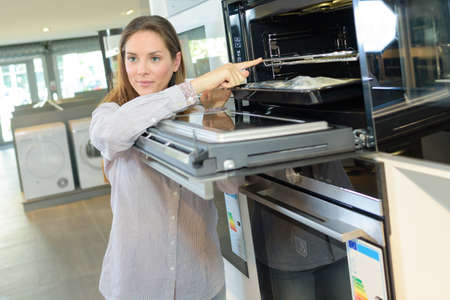 ove: woman looking at ove in home appliance store Stock Photo