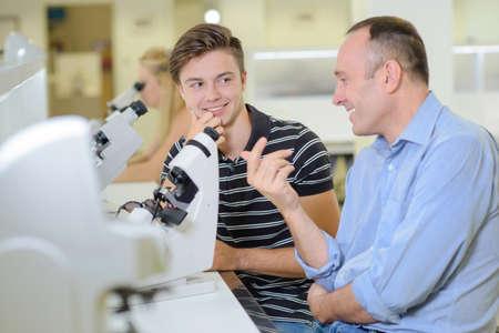 anecdote: Two men chatting next to a microscope Stock Photo