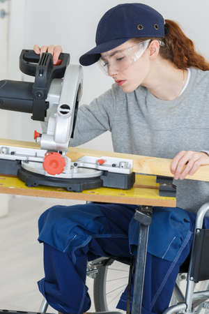 employment: Young woman in wheelchair using circular saw Stock Photo