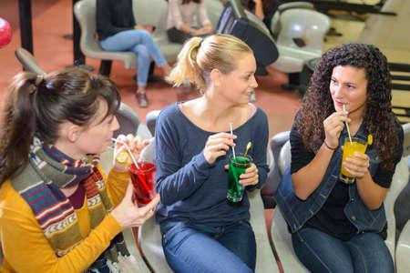Women sipping drinks through straws