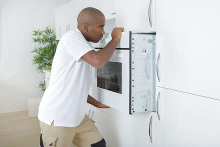 fitting in: Man fitting new oven in kitchen
