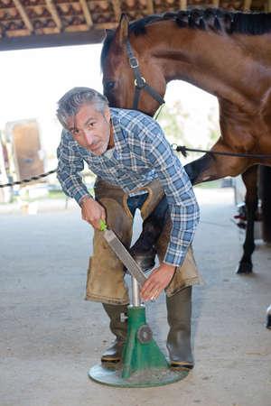 Portriat of farrier filing horses hoof