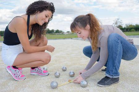 distance: Women measuring distance between bowls