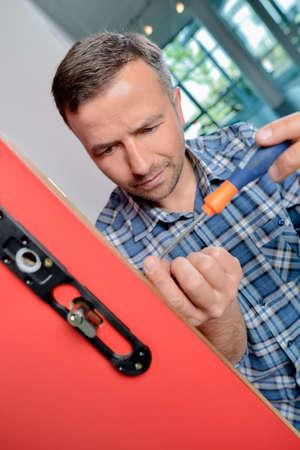 mechanism: man screwing a door lock