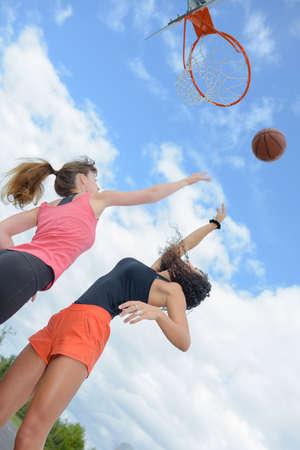 Upward view of two women playing basketball