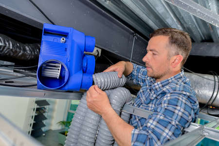 mechanical ventilation: Labourer assembling a forced ventilation