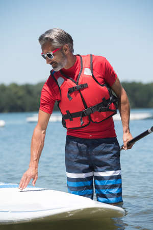 lifevest: man next to a stand-up paddle board on the lake Stock Photo