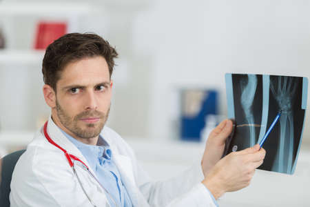 radiogram: male doctor with patient looking at x-ray at office