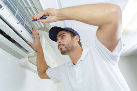 humidify: portrait of mid-adult male technician repairing air conditioner
