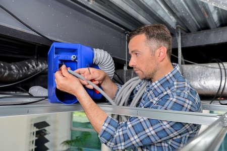heat register: Man repairing ventilation system