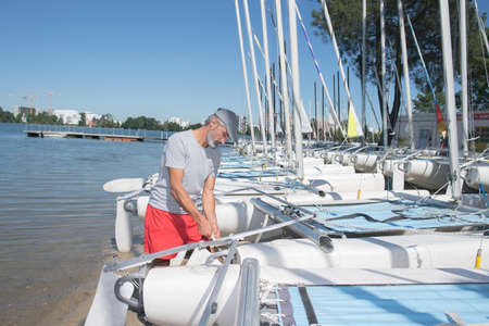 mooring: attractive sailor rigging hobbie-cat before sailing course Stock Photo