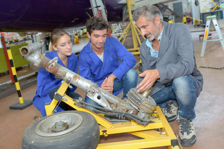 dismantled: Technicians looking at dismantled aircraft landing gear Stock Photo