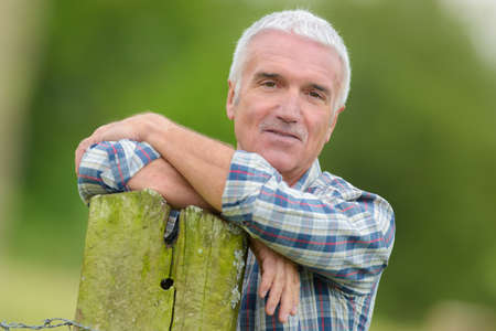 withdrawn: mature man leaning on post