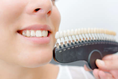 equivalent: Toothy smile next to sample false teeth Stock Photo