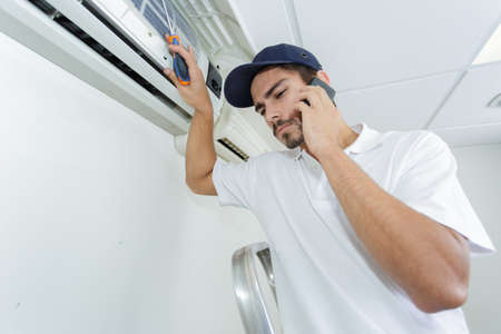 calling for help: young handyman repairing air conditioning system calling for help