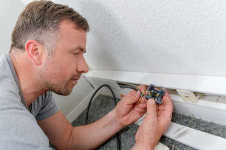 fitting in: Man fitting electrical socket in skirting board