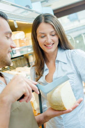 Shop assistant determining with customer where to slice cheese