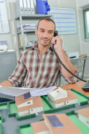 minature: Man on telephone, model houses in front of him